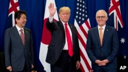President Donald Trump, accompanied by Japanese Prime Minister Shinzo Abe, left, and Australian Prime Minister Malcolm Turnbull, right, waves to reporters at a meeting during the ASEAN Summit at the Sofitel Philippine Plaza, Monday, Nov. 13, 2017, in Mani