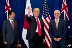 President Donald Trump, accompanied by Japanese Prime Minister Shinzo Abe, left, and Australian Prime Minister Malcolm Turnbull, right, waves to reporters at a meeting during the ASEAN Summit at the Sofitel Philippine Plaza, Nov. 13, 2017.