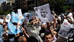 Supporters of presidential candidates Ali Akbar Velayati, shown in the poster at right, and Saeed Jalili, center on the poster, attend a street campaign after Friday prayers, Tehran, Iran, June 7, 2013.