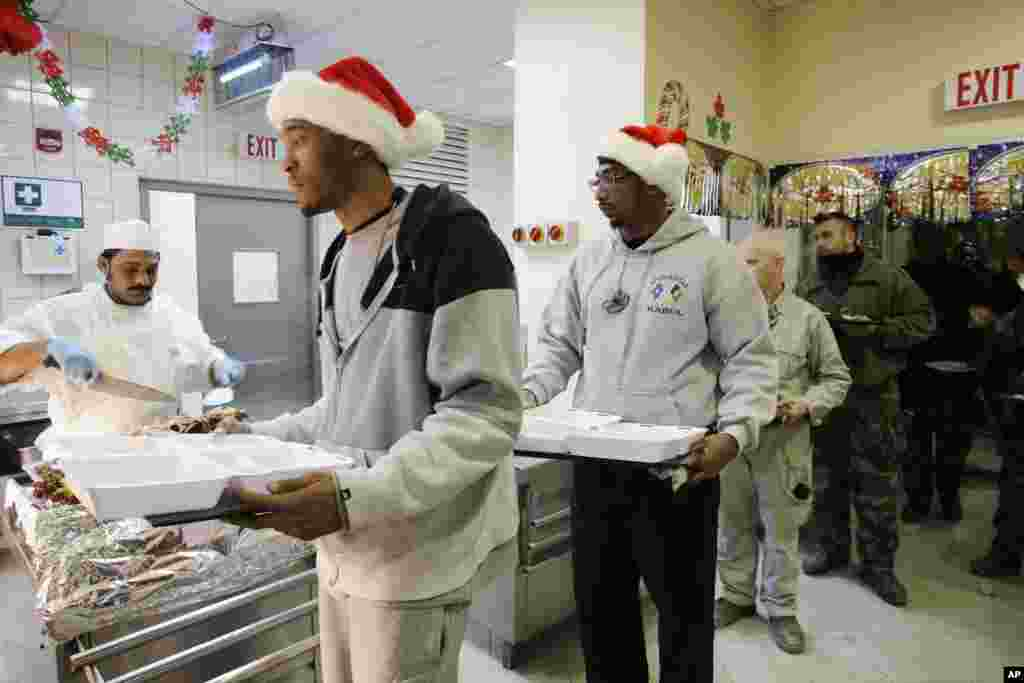 Civilians in Santa Claus hats and service members with the NATO-led International Security Assistance Force wait to be served Christmas dinner at the U.S.-led coalition base in Kabul, Afghanistan, December 25, 2012.