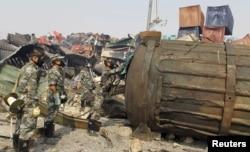 戴着防毒面具的防化兵在天津爆炸现场检查一个大罐子(2015年8月16日)
