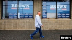 FILE - A pedestrian walks past U.S. election campaign posters in Manchester, New Hampshire.