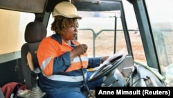 Tene Konate, 42, a truck driver, talks on a radio as she sits in her truck at the gold mine site, operated by Endeavour Mining Corporation in Hounde, Burkina Faso February 10, 2020. (Reuters/Anne Mimault)