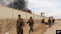 FILE - Smoke rises from a building where Taliban insurgents hid during a fight with Afghan security forces in Helmand province, Afghanistan, March 9, 2016.
