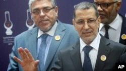 Morocco's new Prime Minister Saadeddine Othmani speaks at the headquarters of the Islamist Justice and Development Party as Moroccan Justice Minister Mustapha Ramid (left) and member of the PJD Mohamed Yatim, look on, in Rabat, Morocco, March 21, 2017. Othmani announced Saturday that he has formed a coalition government.
