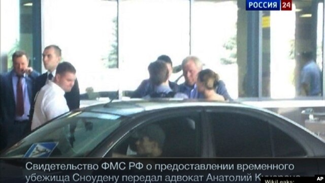 Image released by Russia24 TV channel, shows Russian lawyer Anatoly Kucherena, second right in the center, and National Security Agency leaker Edward Snowden, center back to a camera, Aug. 1, 2013.