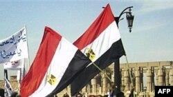 Một số người biểu tình hô khẩu hiệu và phất cờ Ai Cập màu đỏ, trắng và đen