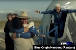 Billionaire businessman Jeff Bezos and pioneering female aviator Wally Funk emerge from their capsule after their flight aboard Blue Origin's New Shepard rocket on the world's first unpiloted suborbital flight near Van Horn, Texas, U.S., July 20, 2021 in