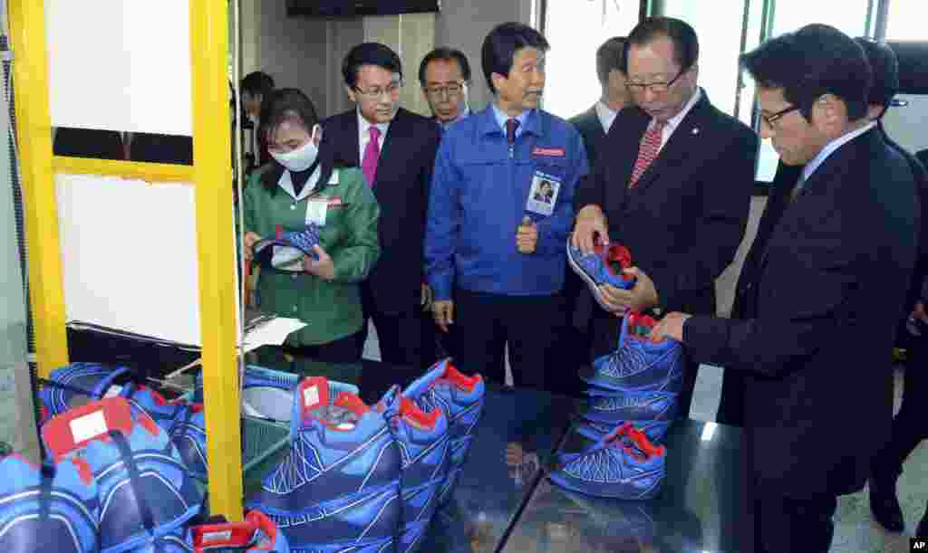 Ahn Hong-joon, chairman of the South Korean National Assembly's Foreign Affairs and Unification Committee, examines a shoe manufactured at a factory at the inter-Korean industrial park in Kaesong, North Korea, Oct. 30, 2013.