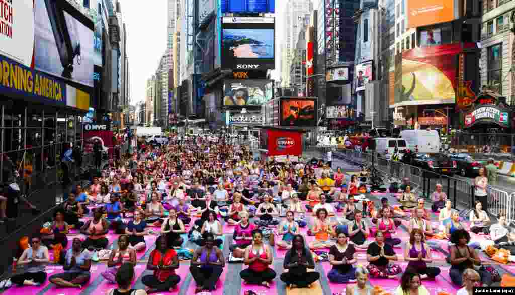 People participate in a group yoga class in Times Square as part of the 14th annual 'Solstice in Times Square: Mind Over Madness Yoga' to mark the summer solstice in New York.