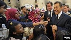 PM Inggris David Cameron (tengah) dan Presiden Perancis Nicolas Sarkozy dielu-elukan oleh massa yang menyalami mereka di Benghazi (15/9).