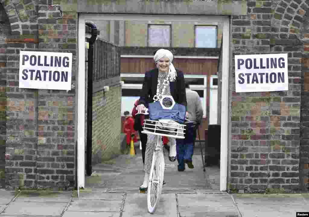 A woman cycles out of a polling station for the referendum on the European Union in Chelsea, London, Britain.
