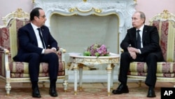 Russian President Vladimir Putin (R) listens to French President Francois Hollande during their meeting in Yerevan, Armenia, April 24, 2015.