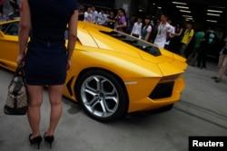 資料照:一名女子站在2012年上海車展的蘭博基尼跑車旁。