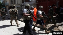Tentara NATO mengamankan lokasi serangan bunuh diri di Kabul, Kamis (16/5).