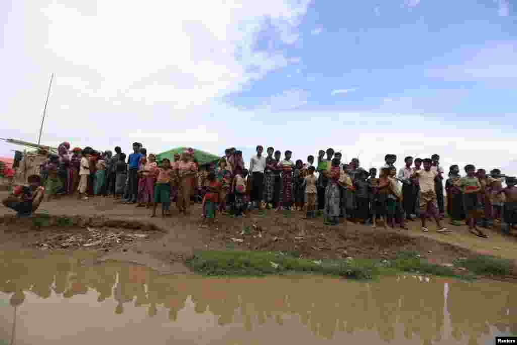 Thandawli villagers stand by the bank of a river in a camp for Rohingya internally displaced persons outside Sittwe, Burma, May 14, 2013.