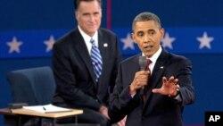 El presidente Barack Obama habla mientras el republicano Mitt Romney escucha sonriente en el fondo. Según las encuestas, Obama ganó el segundo debate.