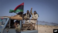 Libyan rebels gesture as they pass the oil refinery in the outskirts of Ras Lanouf, eastern Libya, Sunday, March 27, 2011. Libyan rebels took back a key oil town and pushed westward Sunday toward the capital, seizing momentum from the international airst