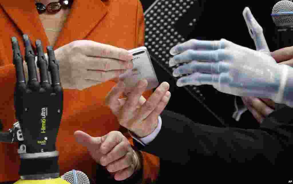Tangan bionik Claudia Breidbach (kanan) yang dikendalikan oleh ponsel tampak menyambut kanselir Jerman Merkel (kiri) dalam pembukaan pameran teknologi di Hannover, Jerman.