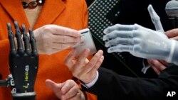 Klaudija Brajdbah pokazuje nemačkoj kancelarki Angeli Merkel svoju veštačku ruku kojom može da upravlja mobilnim telefonom ili Ajfonom, na sajmu kompjutera u Hanoveru 2014.