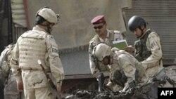 Lực lượng an ninh Iraq xem xét hiện trường sau vụ nổ bom ở thủ đô Baghdad, ngày 22/5/2011