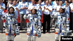 Chinese astronauts (from L to R) Wang Yaping, Zhang Xiaoguang and Nie Haisheng wave before leaving for the Shenzhou-10 manned spacecraft mission at Jiuquan satellite launch center in Jiuquan, Gansu province, June 11, 2013.