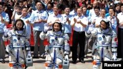 Astronot China (dari kiri) Wang Yaping, Zhang Xiaoguang dan Nie Haisheng melambaikan tangan sebelum memasuki pesawat antariksa Shenzhou-10 di pusat peluncuran pesawat di Jiuquan, propinsi Gansu (11/6).