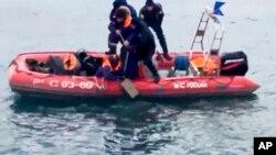 La televisora estatal mostró imágenes de rescatistas en una balsa hinchable portando un contenedor con un objeto naranja brillante cubierto de agua.