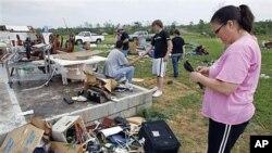 Carla Arenda tente de récupérer quelques effets personnels sur les ruines de sa maison à Vilonia, dans l'Arkansas