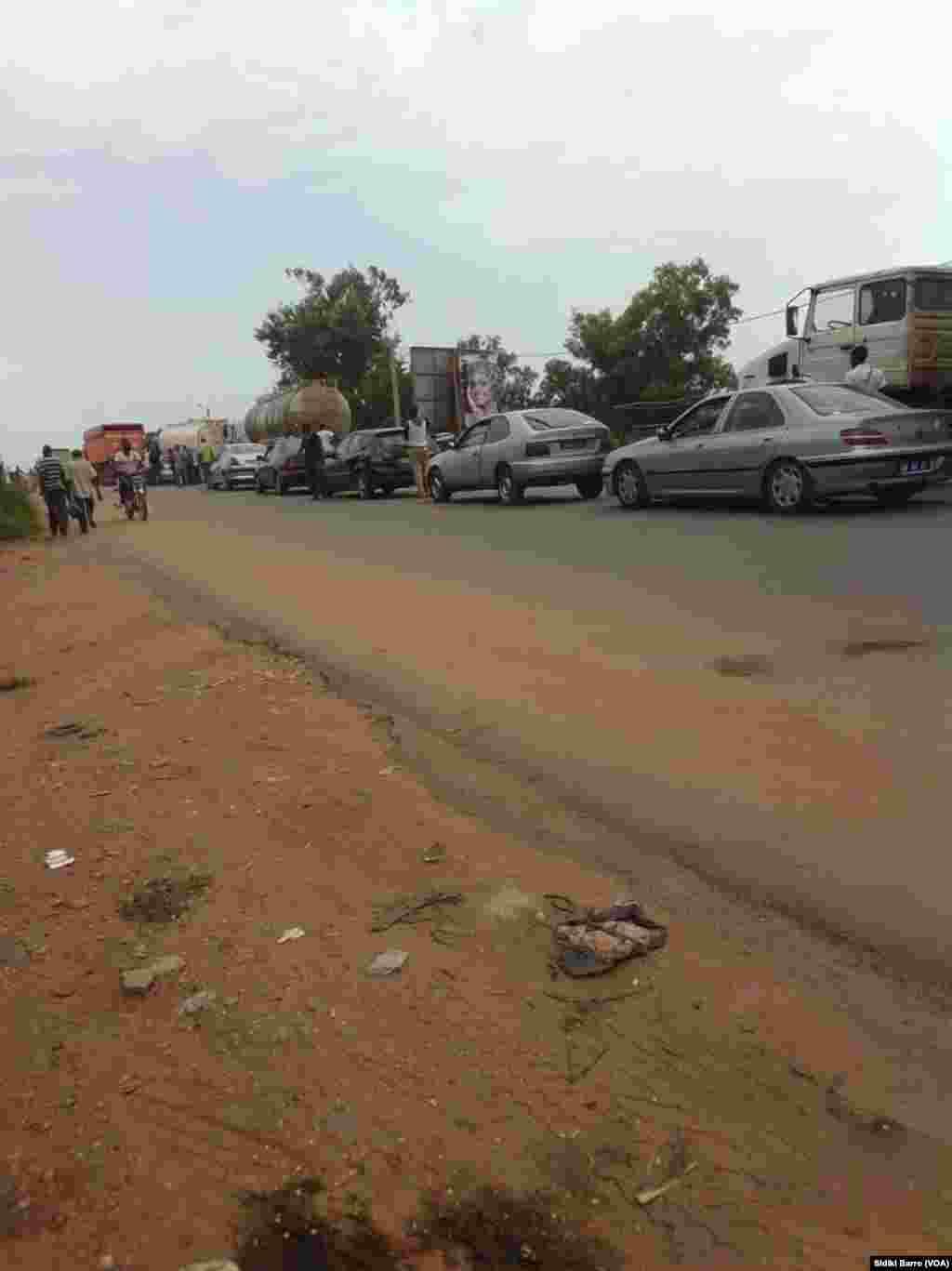 Des taxis et autres voitures sont garés sur le côté de la route à Bouaké, Cote d'Ivoire, 13 mai 2017. (VOA/Sidiki Barro)