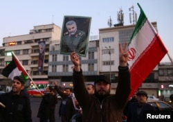 A man holds a picture of late Iranian Major-General Qassem Soleimani, as people celebrate in the street after Iran launched missiles at U.S.-led forces in Iraq, in Tehran, Iran January 8, 2020. Nazanin Tabatabaee/WANA (West Asia News Agency)