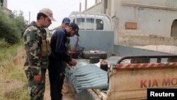 Binh sĩ của phe nổi dậy Syria đứng gần đạn súng cối trên một chiếc xe tải ở thị trấn Khirbet Ghazaleh, thành phố Daraa, ngày 3/5/2013.