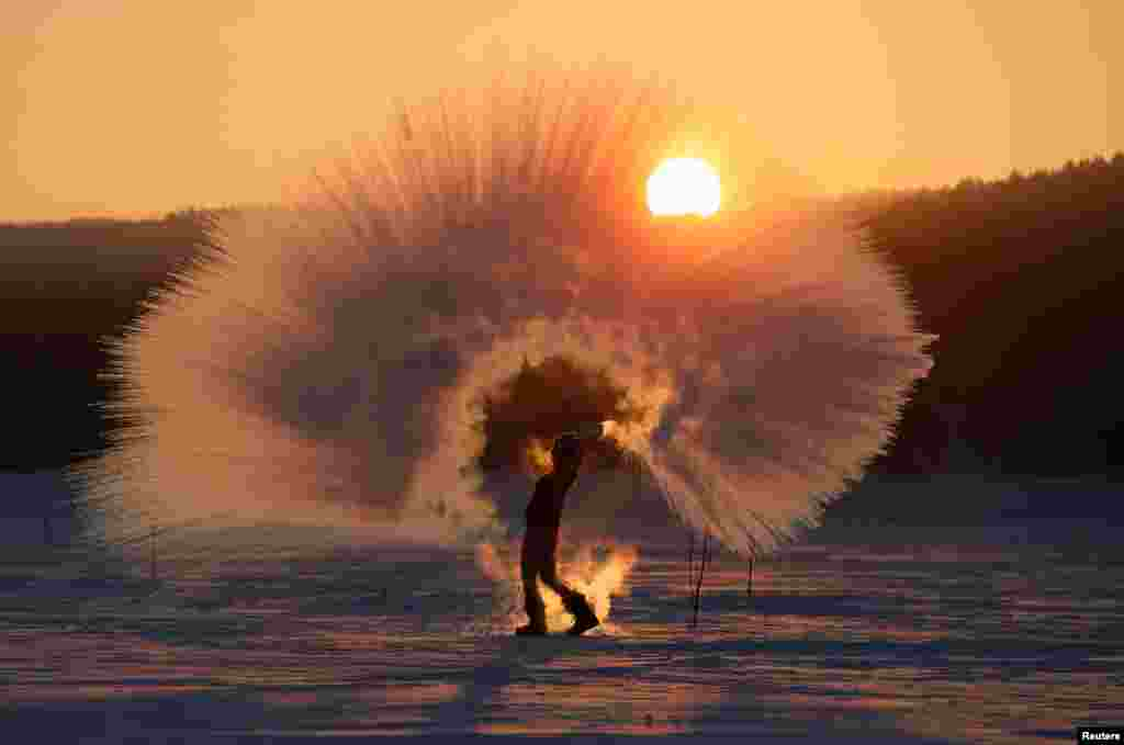 Winter outdoor sports enthusiast Olesya Ushakova poses for an acquaintance (not pictured) while throwing hot water into subzero air as part of the 'Dubak Challenge,' a social media trend popular in Russia, during sunset outside the Siberian city of Krasnoyarsk.