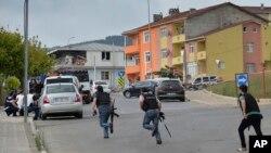 伊斯坦布尔一个警察局附近发生枪战,土耳其警察跑向隐蔽物。 (2015年8月10日)