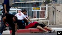 8일 이스라엘 텔아비브에서 의료진이 사망한 팔레스타인 시체를 점검하고 있다. 이 청년은 유대인 4명을 흉기로 찌른 후 이스라엘 경찰이 쏜 총에 맞아 사망했다.