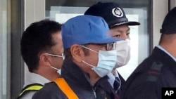 Un hombre cubierto con una máscara facial, que se cree que es el expresidente de Nissan Carlos Ghosn (centro, con gorra azul), sale del Centro de Detención de Tokio, en Tokio, el 6 de marzo de 2019 tras depositar una fianza.