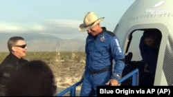 This photo provided by Blue Origin, Jeff Bezos, founder of Amazon and space tourism company Blue Origin, exits the Blue Origin's New Shepard capsule after it parachuted safely down to the launch area. (Blue Origin via AP)