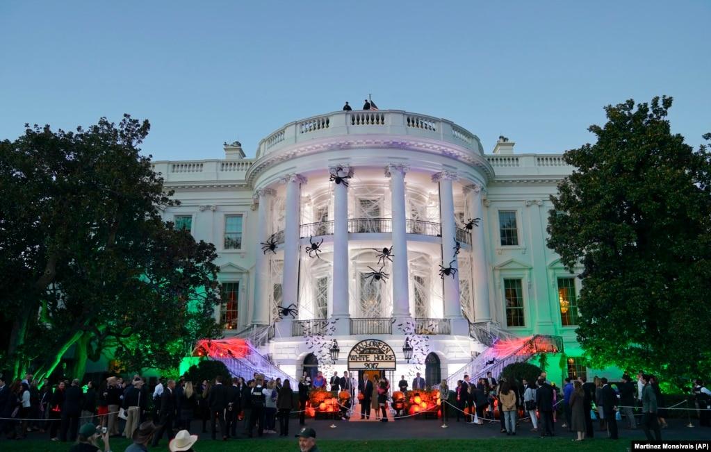 白宫装饰着蜘蛛网、蝙蝠和刻有乔治·华盛顿等前总统形象的橘黄色大南瓜,招待参加万圣节前夜活动的特别来宾(2017年10月31日)。