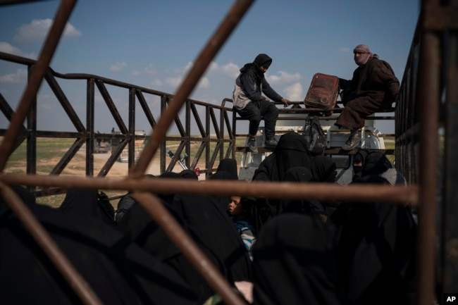 Men, women and children ride in the back of a truck in a convoy evacuating hundreds out of the last territory held by Islamic State militants in Baghuz, eastern Syria, Feb. 22, 2019. Small trucks carrying disheveled men, women and children left the Islamic State group's last pocket of territory in eastern Syria in an escorted convoy on Friday, hours after coalition airstrikes meant to pressure the militants targeted the area on the banks of the Euphrates River.