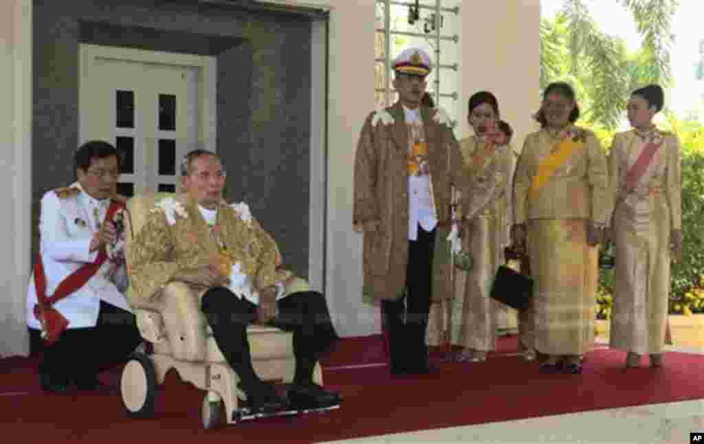 In this photo released by Thailand's Royal Household Bureau, Thai King Bhumibol Adulyadej, second from left, along with Crown Prince Vajiralongkorn, third from left, Princess Chulabhorn, Princess Sirindhorn, and Consort Princess Srirasm, right, arrive at Klai Kangwon Palace before a ceremony in celebration of the king's 86th birthday in Prachuap Khiri Khan province Thailand, Dec. 5, 2013.