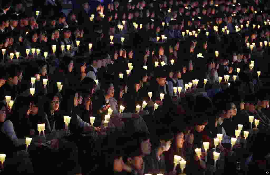 High school students hold candles to pay their respects to the victims of sunken ferry Sewol during a ceremony on the eve of the second anniversary of the sinking in Ansan, South Korea.