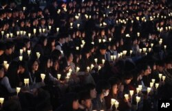 FILE - High school students hold candles to pay their respects to the victims of the sunken ferry Sewol during a ceremony on the eve of the second anniversary of the ferry sinking in Ansan, South Korea, April 15, 2016.