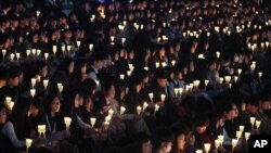 FILE – High school students in Ansan, South Korea, hold candles at a ceremony honoring victims of the Sewol ferry disaster two years earlier off the country's southern coast.