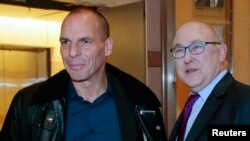 French Finance Minister Michel Sapin (R) and Greek Finance Minister Yanis Varoufakis pose before a meeting at the Bercy Finance Ministry in Paris, Feb. 1, 2015.