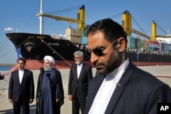 FILE - Iranian President Hassan Rouhani, second left, speaks during the inauguration a newly built extension of the port of Chabahar, near the Pakistani border, on the Gulf of Oman, southeastern Iran, Dec. 3, 2017.