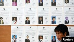 An official sits in front of a board with lists of candidate as she waits for voters at a polling station in Bangkok during a vote to elect a new Senate March 30, 2014.