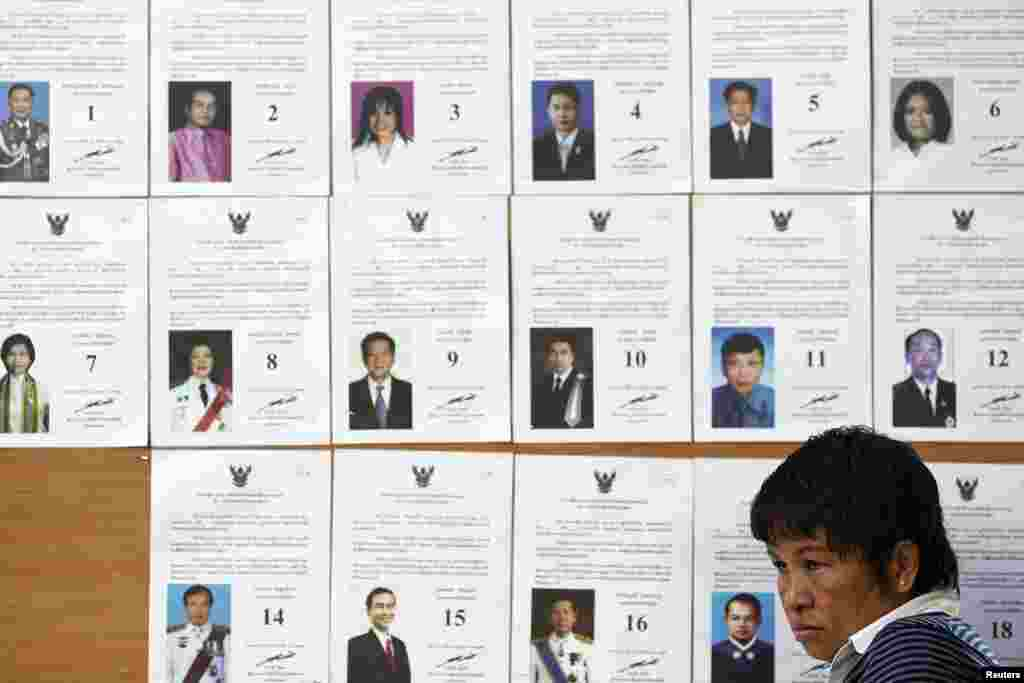 An official sits in front of a board with a list of candidates as she waits for voters at a polling station during a vote to elect a new Senate, in Bangkok, March 30, 2014.