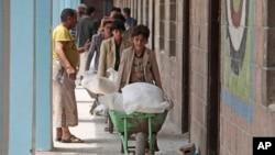 Warga Yaman menerima bantuan makanan dari Badan Pangan Dunia, di sebuah sekolah di Sanaa, Yaman, 25 Agustus 2019. (Foto: AP)