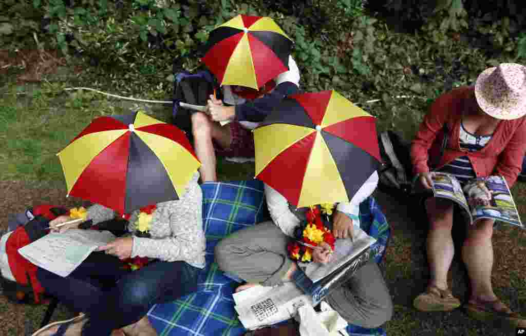 Visitors wearing umbrella hats sit and queue to enter the grounds on the first day at the All England Lawn Tennis Championships in Wimbledon, London.