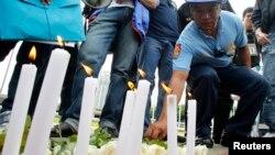 Một cảnh sát viên đốt nến cầu nguyện cho các nạn nhân trong vụ cướp xe buýt hồi năm 2010, tại công viên Luneta ở Manila, Philippines, 23/8/13